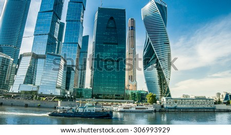 Office buildings stretch up to the blue sky in the financial district in downtown Moscow. River transport. - stock photo