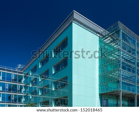Office buildings with glass reflecting surroundings and clear blue sky - stock photo