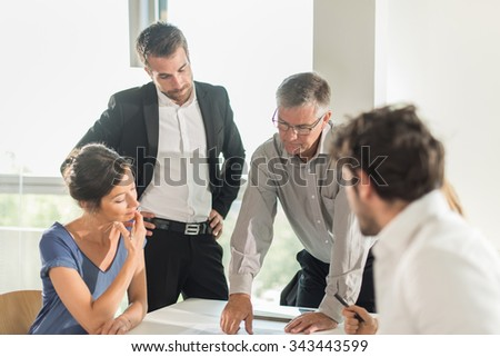 Office business meeting. The team is sitting at a table in a luminous white open space, brainstorming some new ideas. The men are wearing suits and shirts. Everybody is listening to the boss idea
