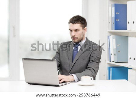 office, business, technology and internet concept - busy businessman with laptop computer and coffee at office