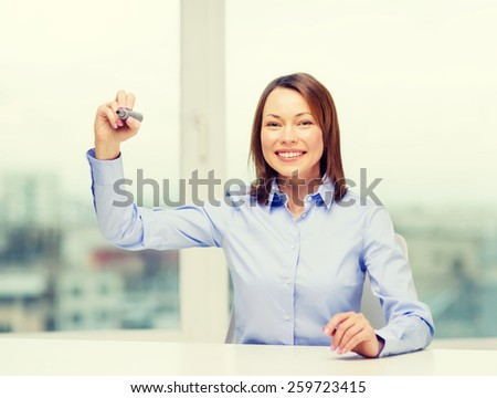 office, business, technology concept - businesswoman writing something in the air with marker - stock photo
