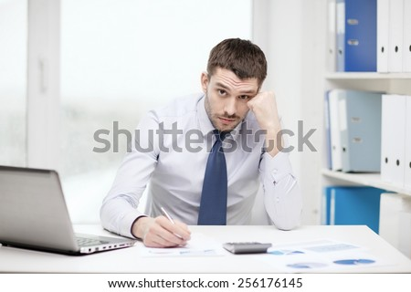 office, business, technology, finances and internet concept - stressed businessman with laptop computer and documents at office - stock photo