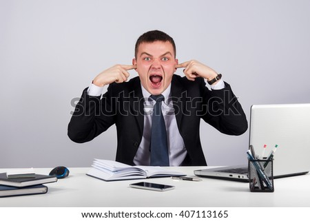Office, business, technology, finances and internet concept-Young businessman shuts his ears with his hands and screaming on gray background - stock photo