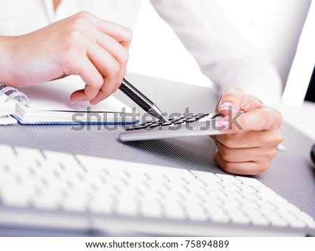Office business woman calculating with calculator and pen