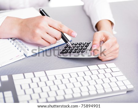 Office business woman calculating with calculator and pencil - stock photo