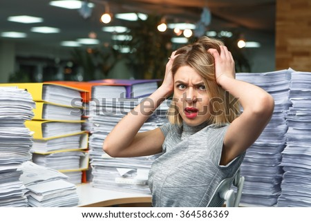 Office businesswoman at her desk full of documents, showing an overwhelmed expression - stock photo