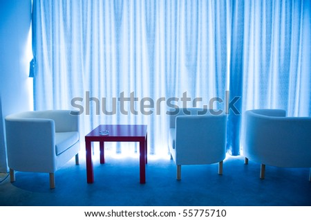 Office cafe bar with comfortable chairs and red table beside curtain. - stock photo