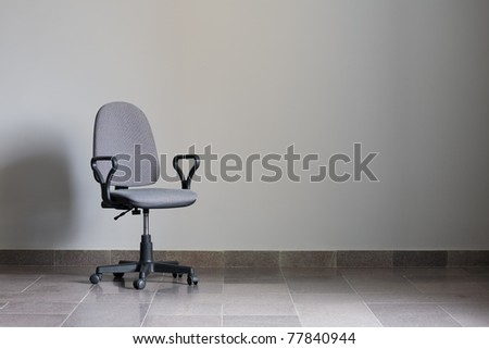 Office chair against a gray wall with sunlight. - stock photo