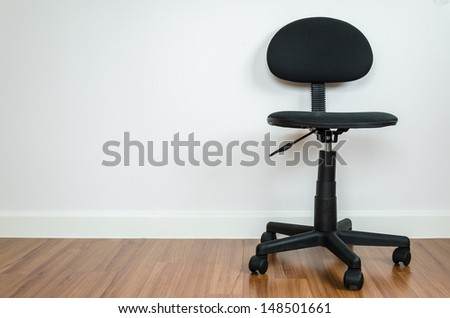 Office chair with white wallpaper - stock photo