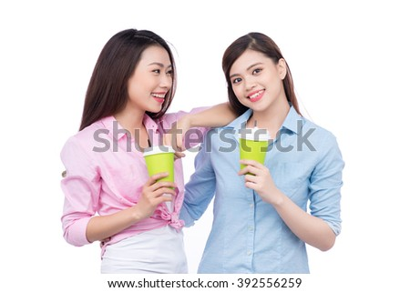 Office coffee break with two female colleagues standing chatting over cups of coffee - stock photo