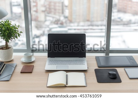 Office. Comfortable work table, workplace with notebook laptop - stock photo