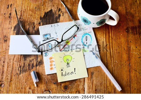 Office composition at the wooden table. Glasses, papers, tea, pen, pencil, with ideas wrote at papers - stock photo