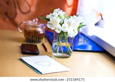 Office composition for St. Valentines Day: bouquet of white freesia flowers, smartphone, pen and notebook with painted heart. Selective focus. Blurred multicolored background. Horizontal image
