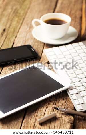 Office concept. Keyboard, tablet pc, and coffee on old wooden table