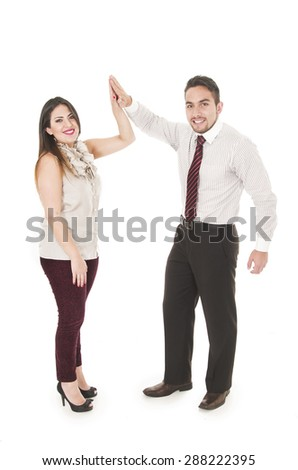 Office couple in formal clothes giving each other high five and smiling to camera - stock photo