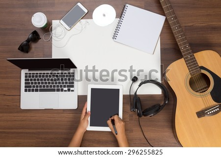 Office desk background, Hand written touchscreen on tablet PC with acoustic guitar, headphones recording scene project ideas concept. mobile phones, laptop computer, View from above with copy space - stock photo