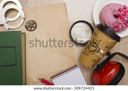 Office desk cop with handcuffs, a police star, coffee and donuts. - stock photo