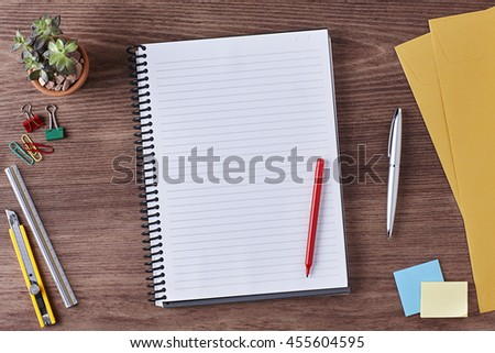Office Desk Table with a Blank Notebook, Paper, Ruler, Pencil, Red Pen, Envelope, Plant Pot, Clips and Supplies. Workplace. Top View on a Wooden Background with Copy space for text or Image