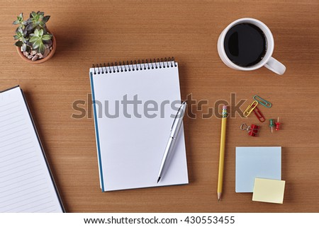 Office Desk Table with a Blank Notebook, Plant Pot, Cup of coffee, Pen, Pencil, Piece of Paper and Supplies. Workplace Top View on a Wooden Background with Copy space for text or Image - stock photo