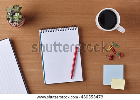 Office Desk Table with a Blank Notebook, Plant Pot, Cup of coffee, Red Pen, Piece of Paper and Supplies. Workplace Top View on a Wooden Background with Copy space for text or Image - stock photo