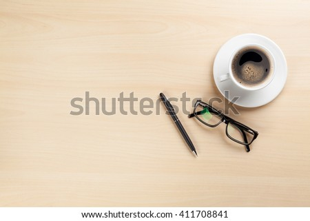 Office desk table with coffee cup, pen and glasses. Top view with copy space - stock photo