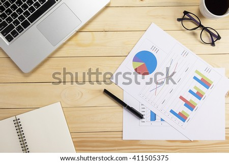Office desk table with computer, supplies, analysis chart, pen, eyeglasses. Top view with copy space (selective focus)  - stock photo