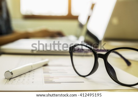 Office desk table with computer, supplies, analysis chart, pen, eyeglasses with copy space.vintage tone Retro filter effect,soft focus,low light.(selective focus)(selective focus)