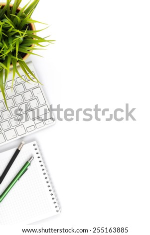 Office desk table with computer, supplies and flower. Isolated on white background. Top view with copy space - stock photo