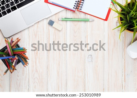 Office desk table with computer, supplies and flower. Top view with copy space - stock photo