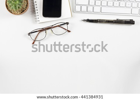 Office desk table with computer, supplies, cactus,glasses,working place elements on white table,White office desk table with a lot of things on it. Top view with copy space.selective focus - stock photo