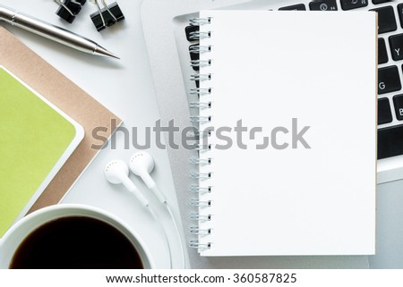 Office desk table with laptop computer, notebooks, a cup of coffee, pen and earphone . Top view. The white blank notebook page can be added images, texts or the art works. - stock photo