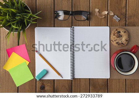 Office desk table with notebook, supplies, coffee cup and flower - stock photo