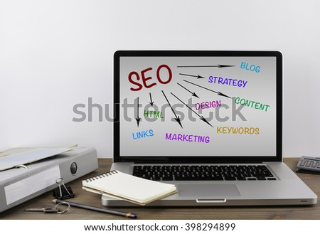 Office desk with a laptop. SEO concept - stock photo