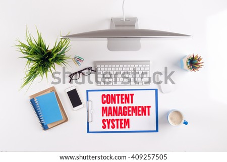 Office desk with CONTENT MANAGEMENT SYSTEM paperwork and other objects around, top view - stock photo