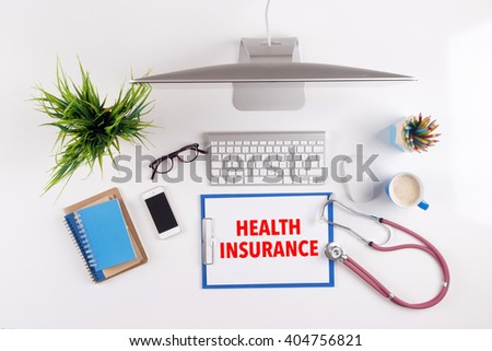 Office desk with HEALTH INSURANCE paperwork and other objects around, top view - stock photo