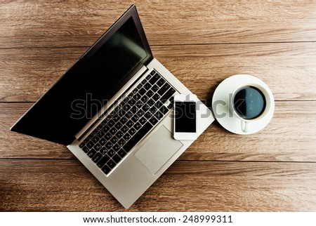 Office desk with laptop computer,  mobile smartphone and coffee cup.  - stock photo