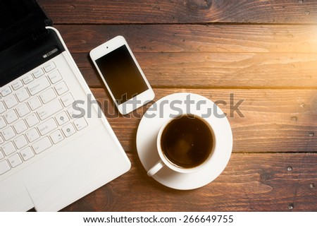 Office desk with laptop computer, notebook, mobile smartphone and coffee cup on wood,morning light - stock photo
