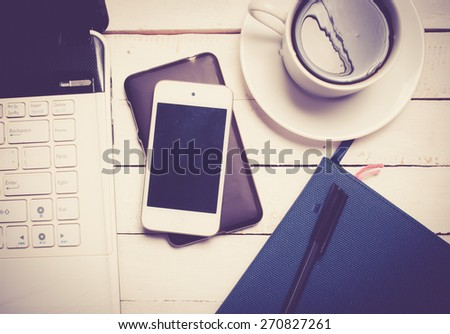 Office desk with laptop computer, notebook, mobile smartphone and coffee cup on wood,vintage color toned image - stock photo
