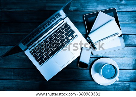 Office desk with laptop computer, tablet pc, planner, pen, mobile smartphone and coffee cup  - stock photo