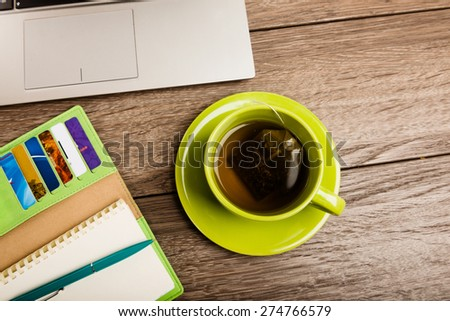 Office desk with laptop computer, tablet pc, planner, pen, mobile smartphone and cup of tea.
