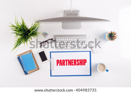 Office desk with PARTNERSHIP paperwork and other objects around, top view - stock photo