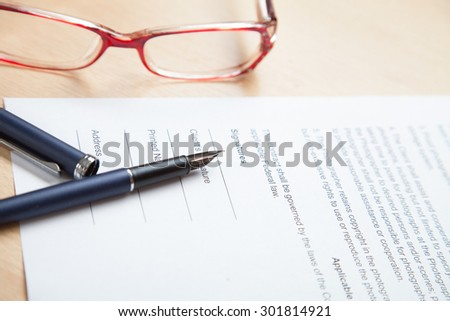 Office desk with pen, glasses and paper - stock photo