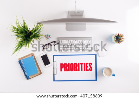 Office desk with PRIORITIES paperwork and other objects around, top view - stock photo