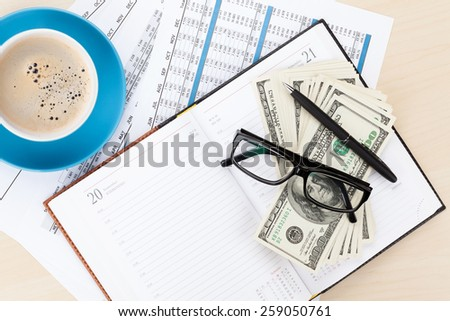 Office desk with reports, blank notepad and money cash. View from above with copy space - stock photo