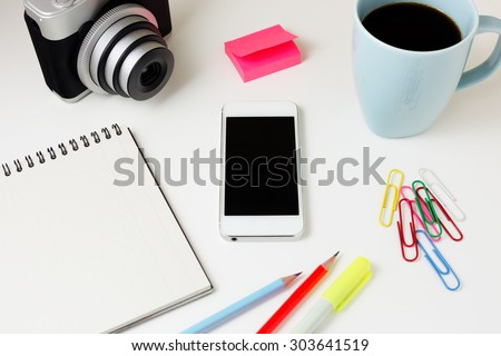 Office desk with smart phone, camera, notebook, coffee mug, paperclip and pencil - stock photo