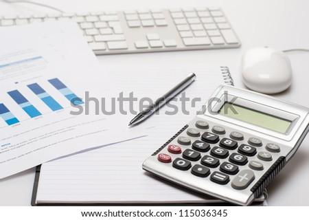 Office desk with supplies calculator pen notepad keyboard and mouse - stock photo