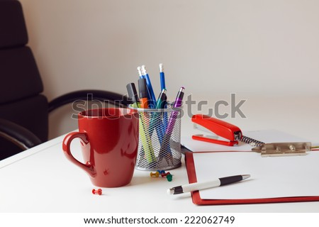 Office desk with various items including coffee cup and stationary - stock photo