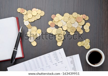 Office desk with world map made of money coins and agenda - stock photo