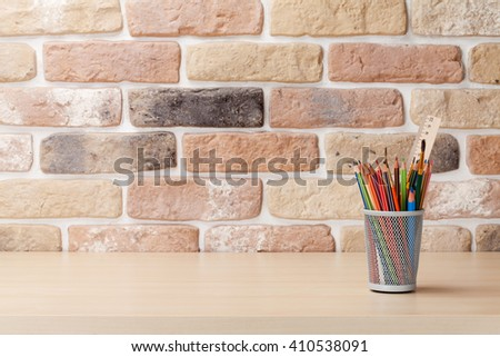 Office desk workplace table in front of brick wall. View with copy space - stock photo