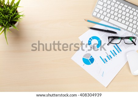 Office desk workplace with pc, charts and plant on wooden table. Top view with copy space
